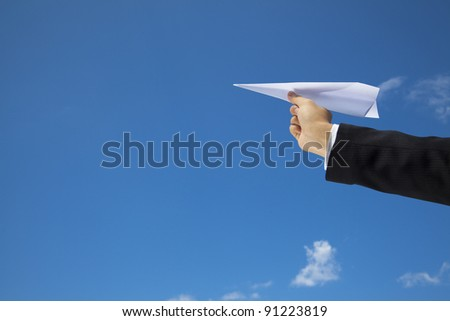 hand of Businessman letting an airplane made of paper fly over blue sky - stock photo