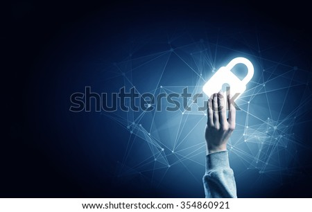 Hand of businessman on dark background with security glowing sign - stock photo