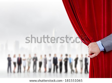Hand of businessman opening red velvet curtain - stock photo