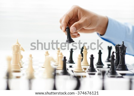 Hand of businessman playing chess - stock photo