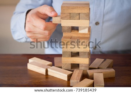 hand of businessman pulling out or placing wood block on tower