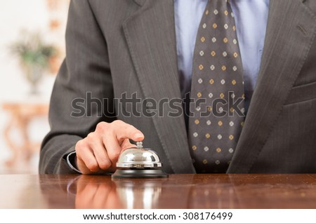 hand of businessman ringing hotel bell in reception desk close up selective focus - stock photo