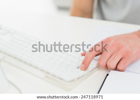 Hand of businessman typing on keyboard in his office