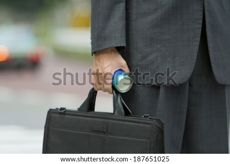 hand of businessman with bag and canned drink - stock photo