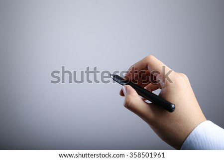 Hand of businessman writing on the blank gradually varied background. - stock photo