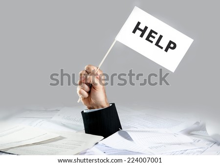 Hand of caucasian businessman emerging from office desk loaded of paperwork , invoices and a lot of papers and documents holding white flag  asking for help  - stock photo