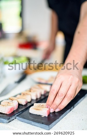Hand of Chef preparing sushi in the kitchen - stock photo