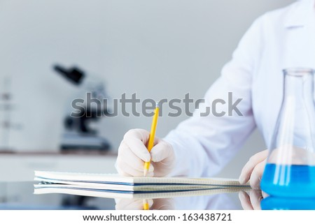 Hand of chemist with pencil writing down observations in laboratory - stock photo