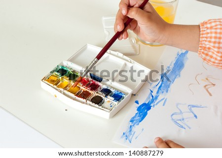Hand of child with paintbrush taking paint on watercolor set - stock photo