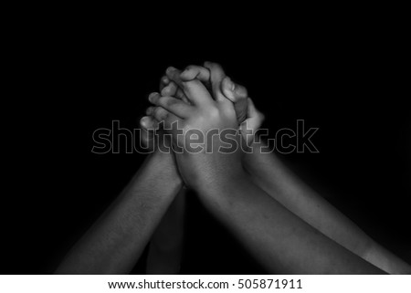 hand of children raised up on black background in white tone with shadow edge