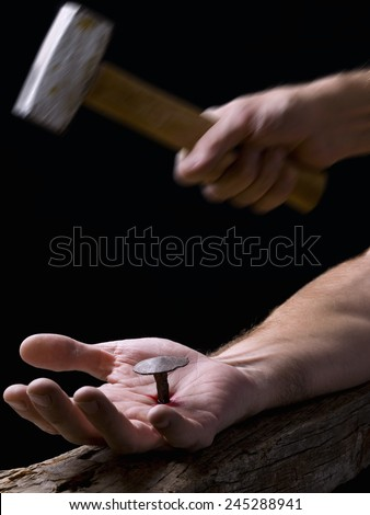 Hand of Christ, nailed to the cross, and bottom, a hand with a hammer - stock photo