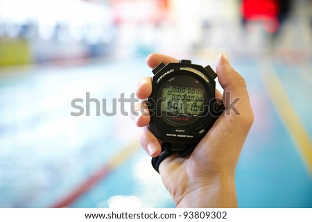 hand of coach with a stopwatch during competitions in the swimming pool - stock photo