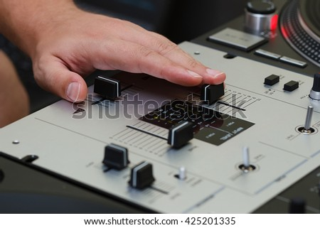 Hand of DJ mixing music on professional sound controller and turntable vinyl record player. Focus on hands, knobs and regulators.  - stock photo
