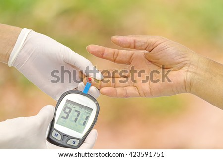 Hand of doctor checking for blood glucose meter, the blood sugar value is measured on a finger and pink bokeh background. - stock photo