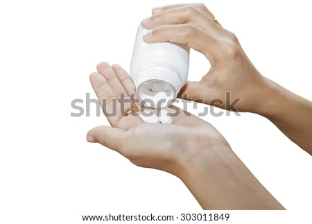 hand of doctor holding Many pills and tablets and medicine out of a bottle isolated on white background - stock photo