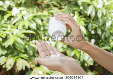 hand of doctor holding Many pills and tablets and medicine out of a bottle on nature background - stock photo