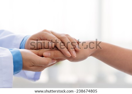 Hand of doctor reassuring her female patient - stock photo