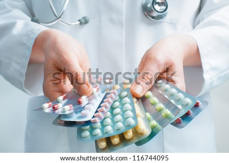 Hand of doctors holding many different pills - stock photo