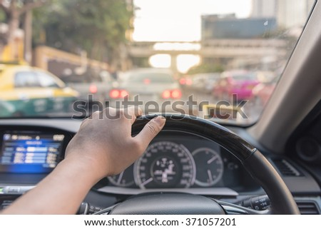 hand of driver on steering wheel of car - vintage picture style