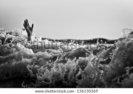 Hand of drowning man trying to swim out of the stormy ocean. Black and white photo. - stock photo