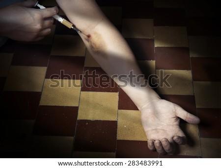 Hand of drug user in the dark interior with opium syringe - stock photo