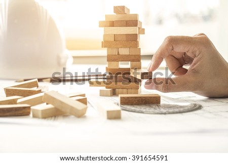 Hand of engineer playing a blocks wood game on blueprint or architectural project vintage tone.