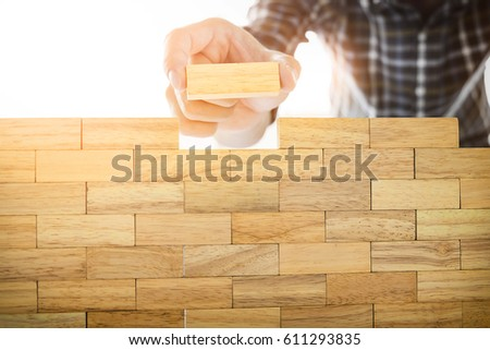 Hand of engineer playing a blocks wood tower game on blueprint or architectural project concept