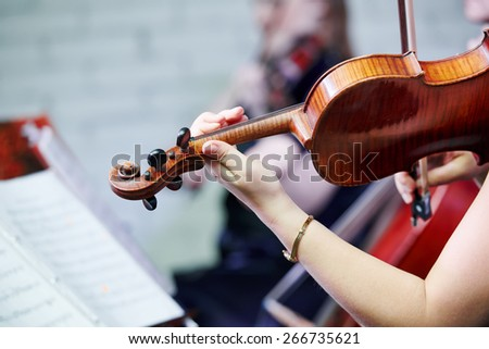 Hand of female violin player musician playing music at entertainment party  - stock photo