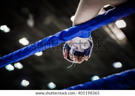 hand of fighter on ropes of ring during competition in mixed martial arts - stock photo