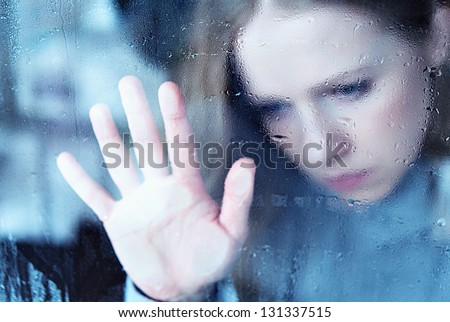 hand of girl melancholy and sad  at the window in the rain - stock photo