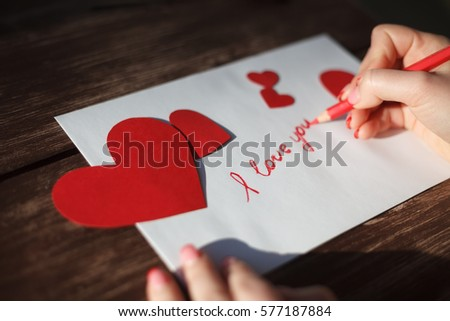 Hand girl writing love letter on stock photo royalty free hand of girl writing love letter on saint valentines dayhandmade postcard with red heart spiritdancerdesigns Gallery