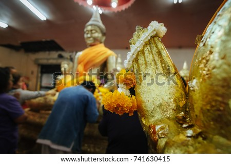 Hand of golden Buddha statue and flower garland with blur Buddha statue background