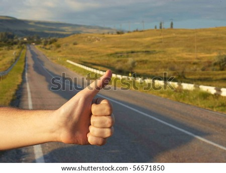 Hand of hiker man at rural mountain road. Daybreak. - stock photo