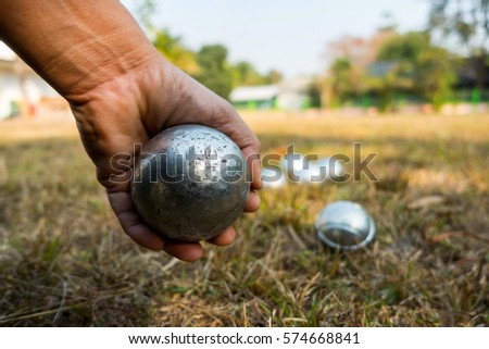 Hand of holding petanque ball. people at sport playing game petanque.