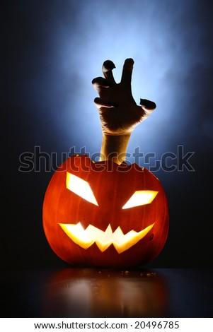 Hand of horror raising from glowing pumpkin lantern. - stock photo
