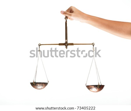 Hand of judge holding scales in isolation - stock photo