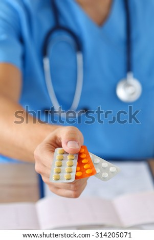 Hand of male medicine doctor wearing blue uniform holding pack of different tablet blisters closeup. Medical prescription, pharmacy or insurance concept. Giving or showing medications to patient - stock photo
