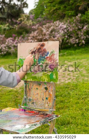 Hand of male painter finishing his sketch on an old sketchbook during an art class in a park - stock photo