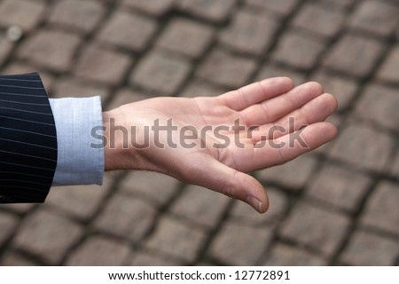 Hand of man against pavement, close-up - stock photo