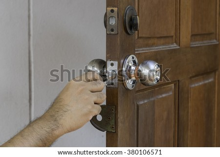 hand of man and locksmith on old wood door - stock photo