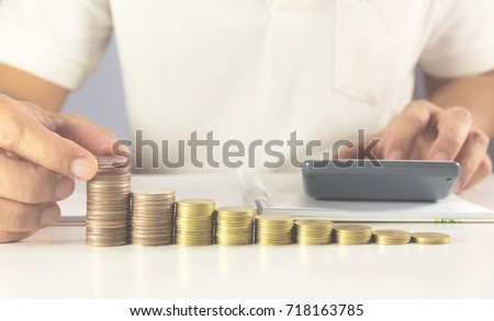 Hand of man are pressing the calculator with stack coins on the table. Man pressing calculator button. Financial analyzing concept.