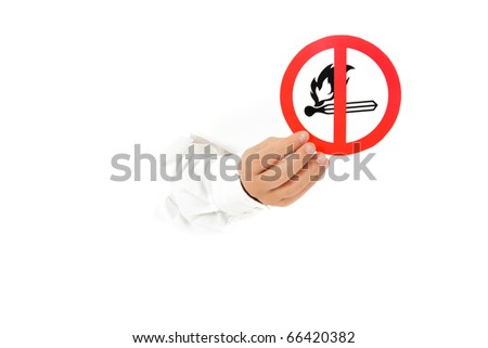 """Hand of man breaking through a paper wall and showing """"no fire in area"""" warning sign. Copy space. Studio shot. White background. - stock photo"""