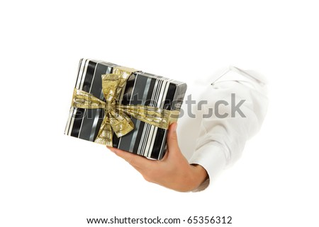 Hand of man breaking through a paper wall holding gift box with golden bow . Copy space. Studio shot. White background. - stock photo