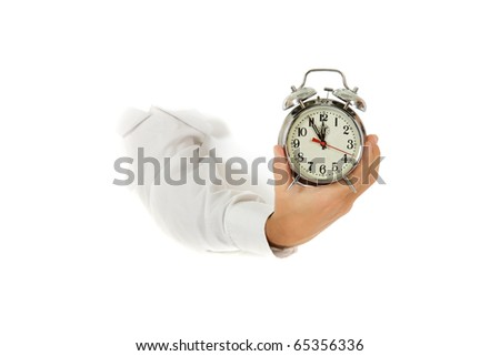 Hand of man breaking through a paper wall holding retro alarm clock. Copy space. Studio shot. White background. - stock photo