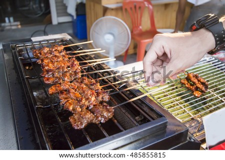 hand of man cooking barbecue