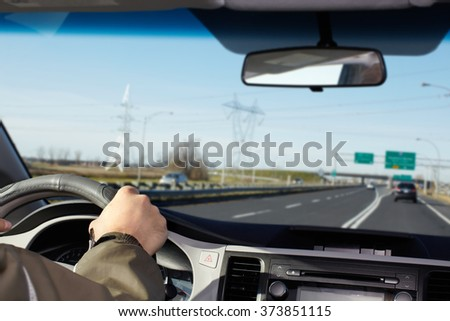 Hand of man driving on a highway. - stock photo