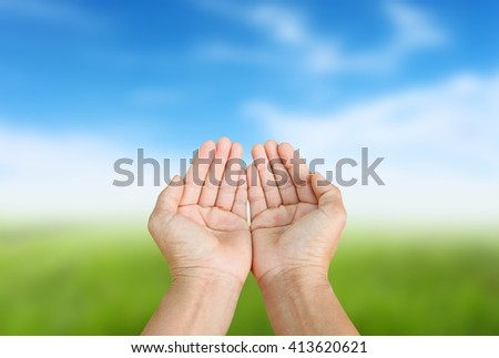 Hand of man praying to God on sky background .