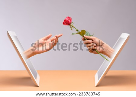 Hand of man presenting a rose to his internet girlfriend - stock photo