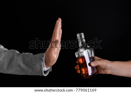 Hand of man rejecting bottle of alcohol against dark background