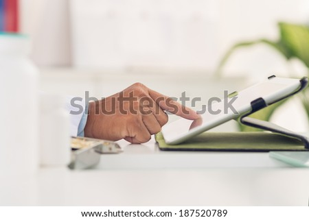 Hand of man using digital tablet - stock photo